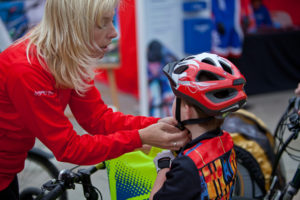 Woman helping child fit a bike helmet