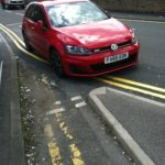 Red car Parked on double yellow blocking bike lane